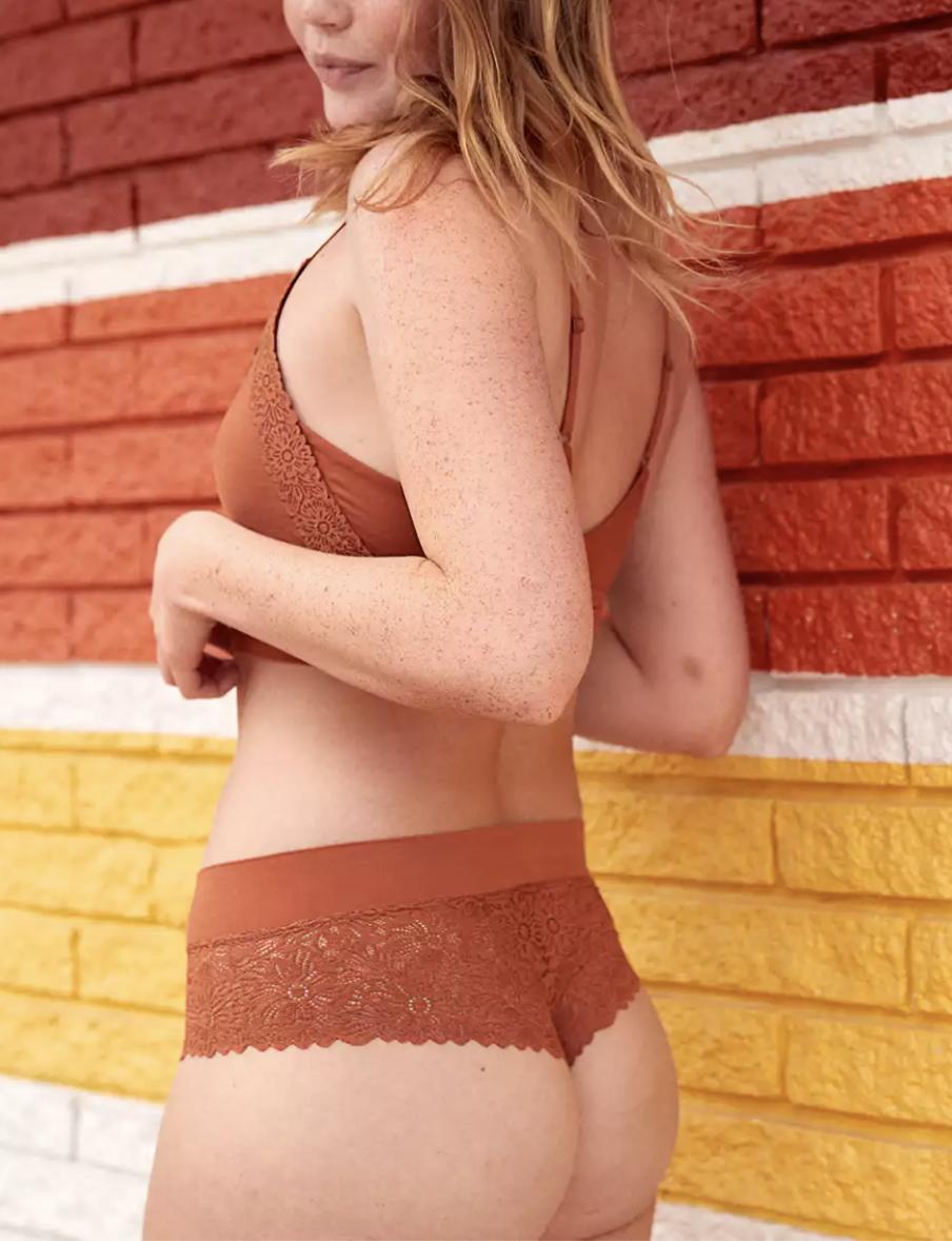 a model wearing the floral lace cheeky underwear in orange