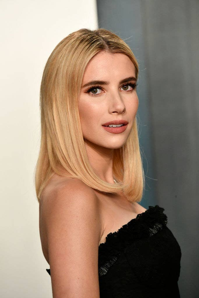 Emma Roberts posing on a red carpet in a strapless outfit