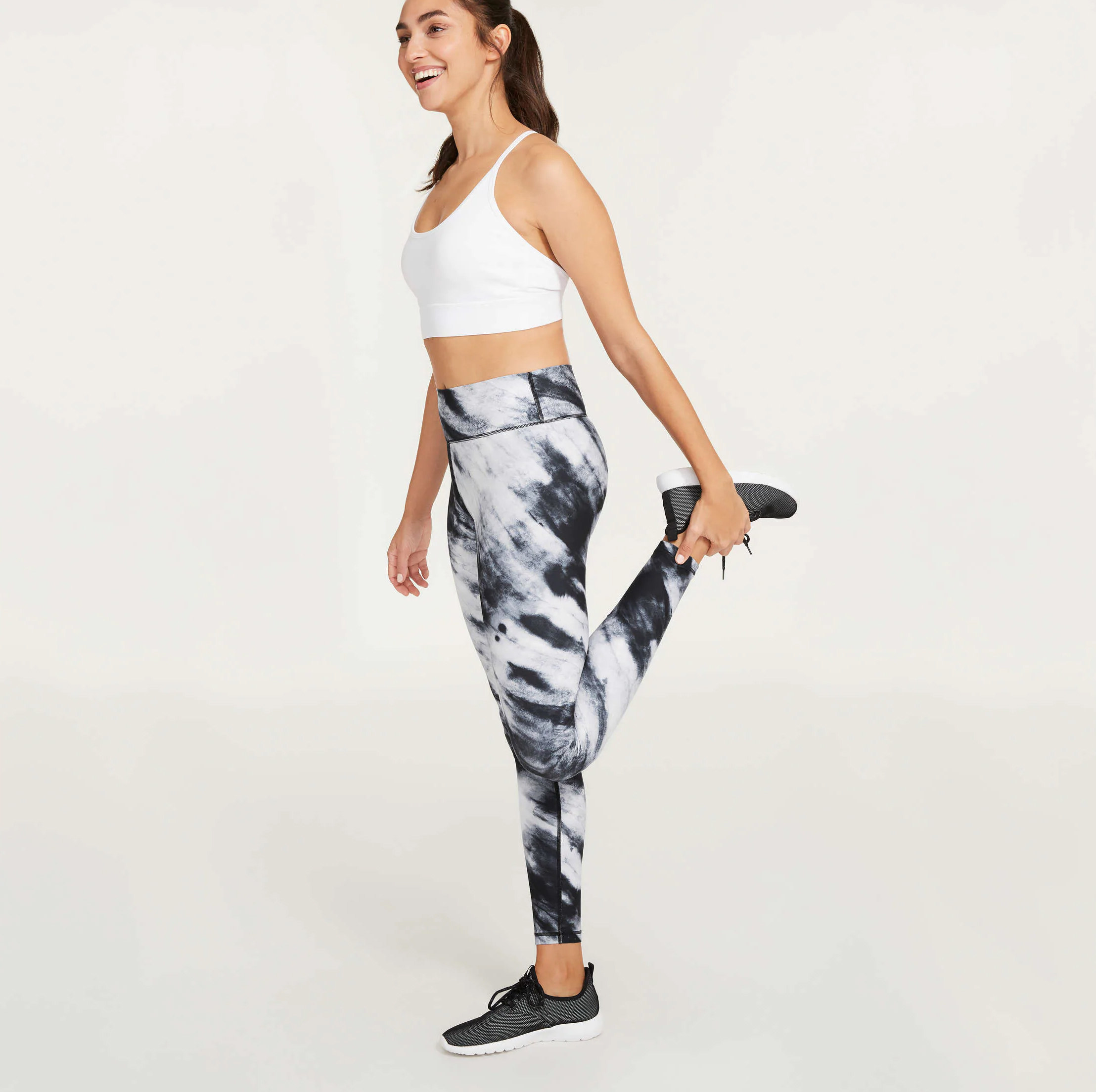 A person wearing a sports bra and patterned leggings