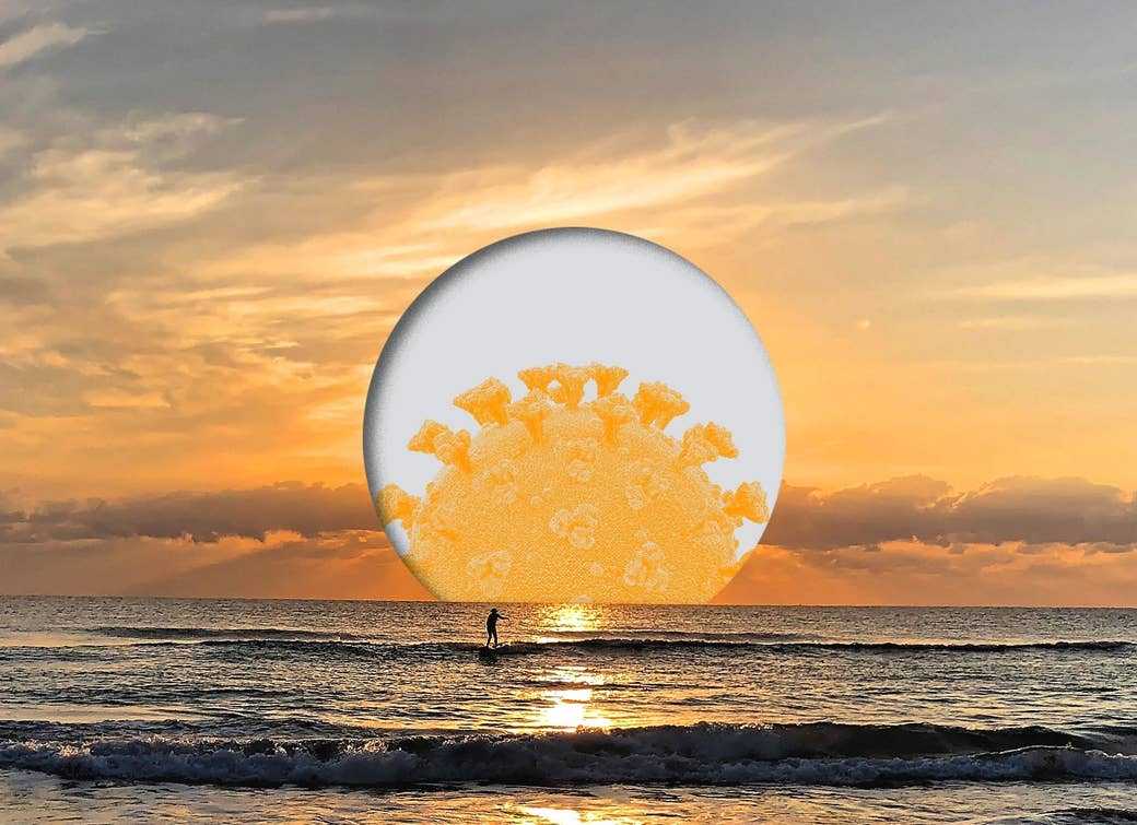 A surfer rides a wave as the sun, illustrated with a coronavirus germ, sets behind them