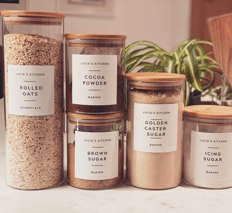 "Six of the customized labels which read ""Lucie's Kitchen"" and rolled oats, cocoa powder, brown sugar, golden caster sugar, and icing sugar"