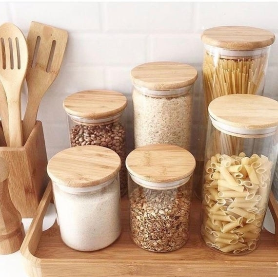 Six of the bamboo and glass jars filled with pasta, rice, beans, and oats