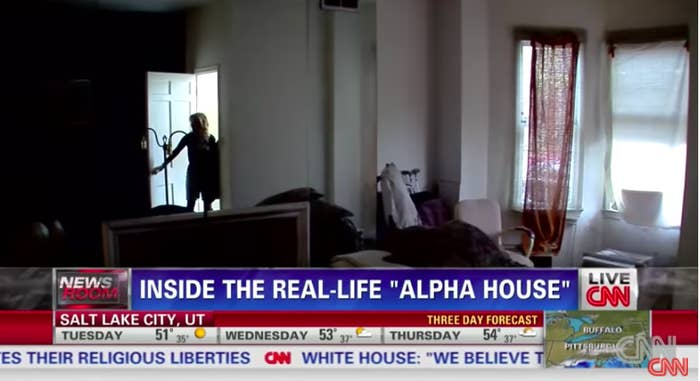 A person opening the front door into the darkened house that has items strewn about