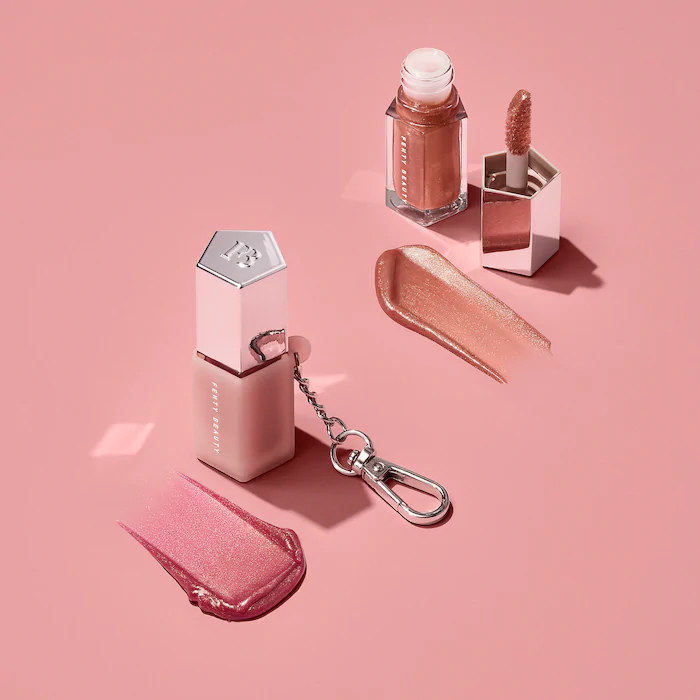 Two mini tubes of lip gloss on a plain background