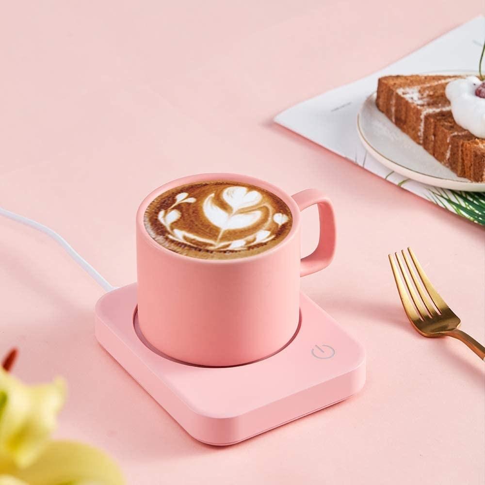 A pink mug warmer on a desk with a mug onf coffee on it