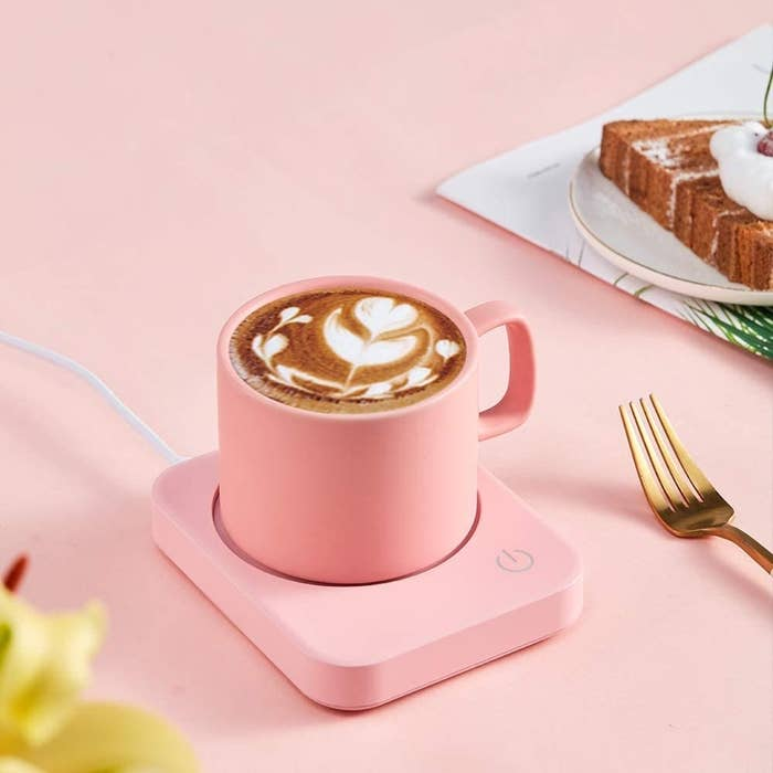 A pink mug warmer on a desk with a mug of coffee on it