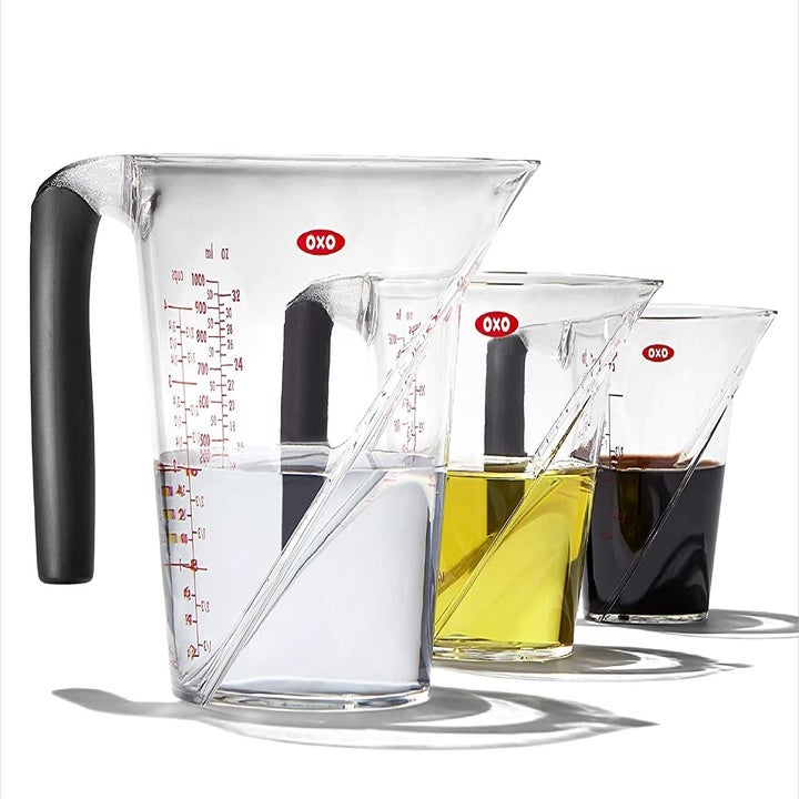 Three different-sized measuring cups filled with different-colored liquids