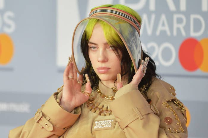 Billie Eilish posing at the Brit Awards 2020 wearing a Burberry London coat, a clear visor, and long nails featuring the Burberry's signature and iconic tartan print