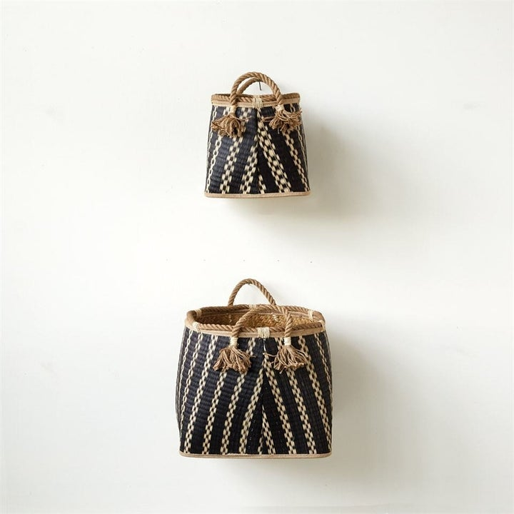 Two woven baskets in different sizes with two tone pattern and handles, hanging on a wall