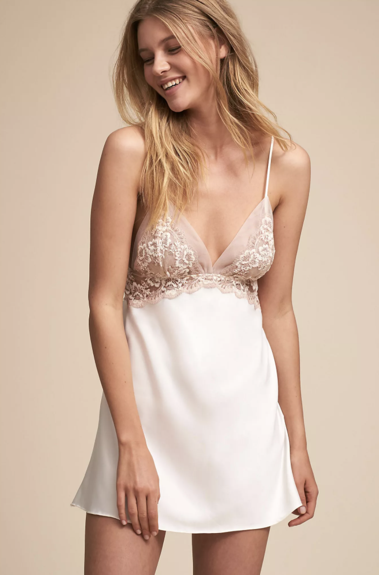 a model in a white chemise with a nude bra top and white lace over the bra