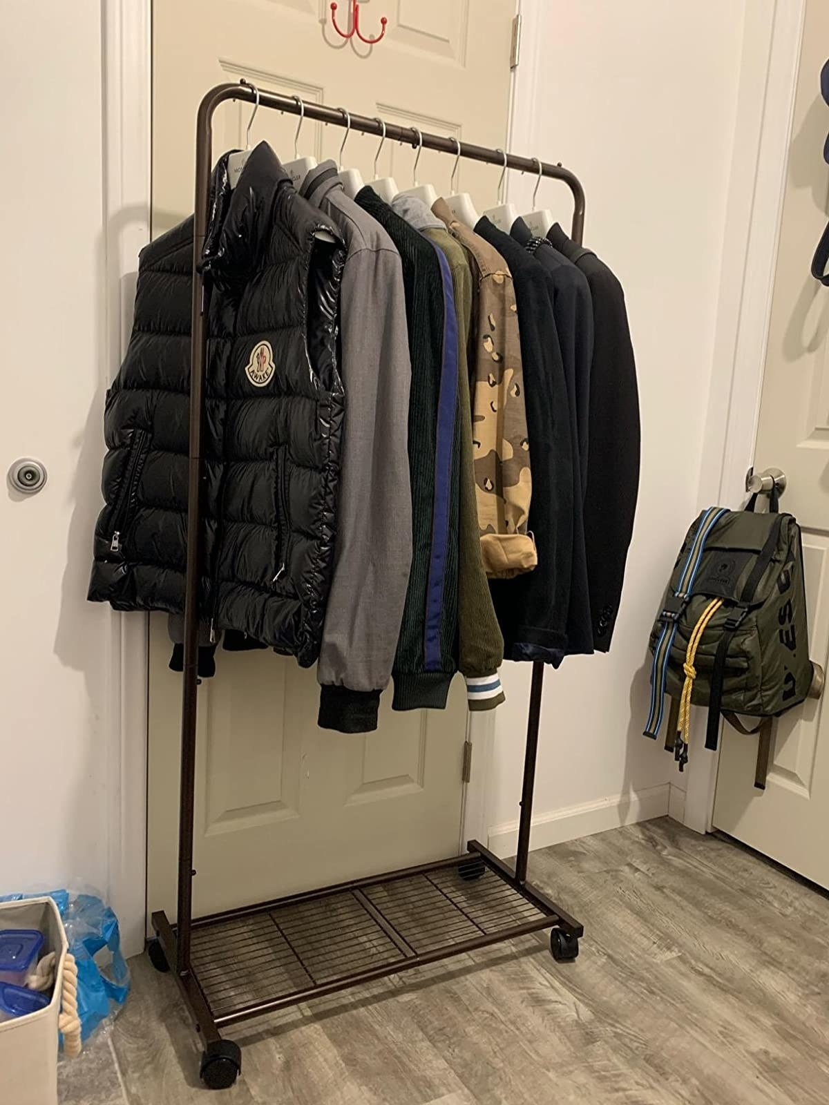 reviewer image of coats on hangers hanging from a customer's simple garment rack