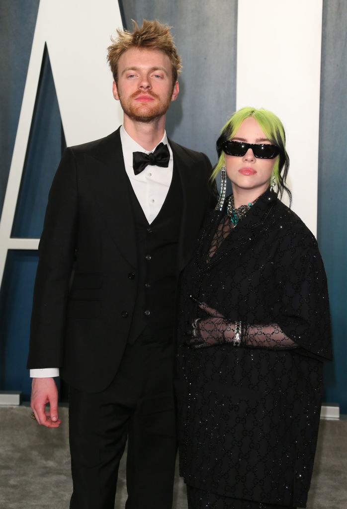 Finneas and Billie, wearing sunglasses, posing on a red carpet with their arms around each other
