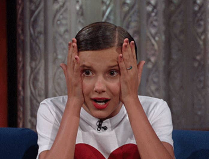 Millie Bobby Brown grabs her face in shock during an interview