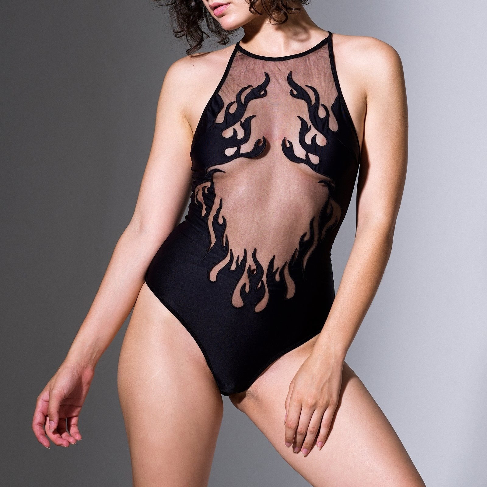 a model in a black body suit with cut out flames