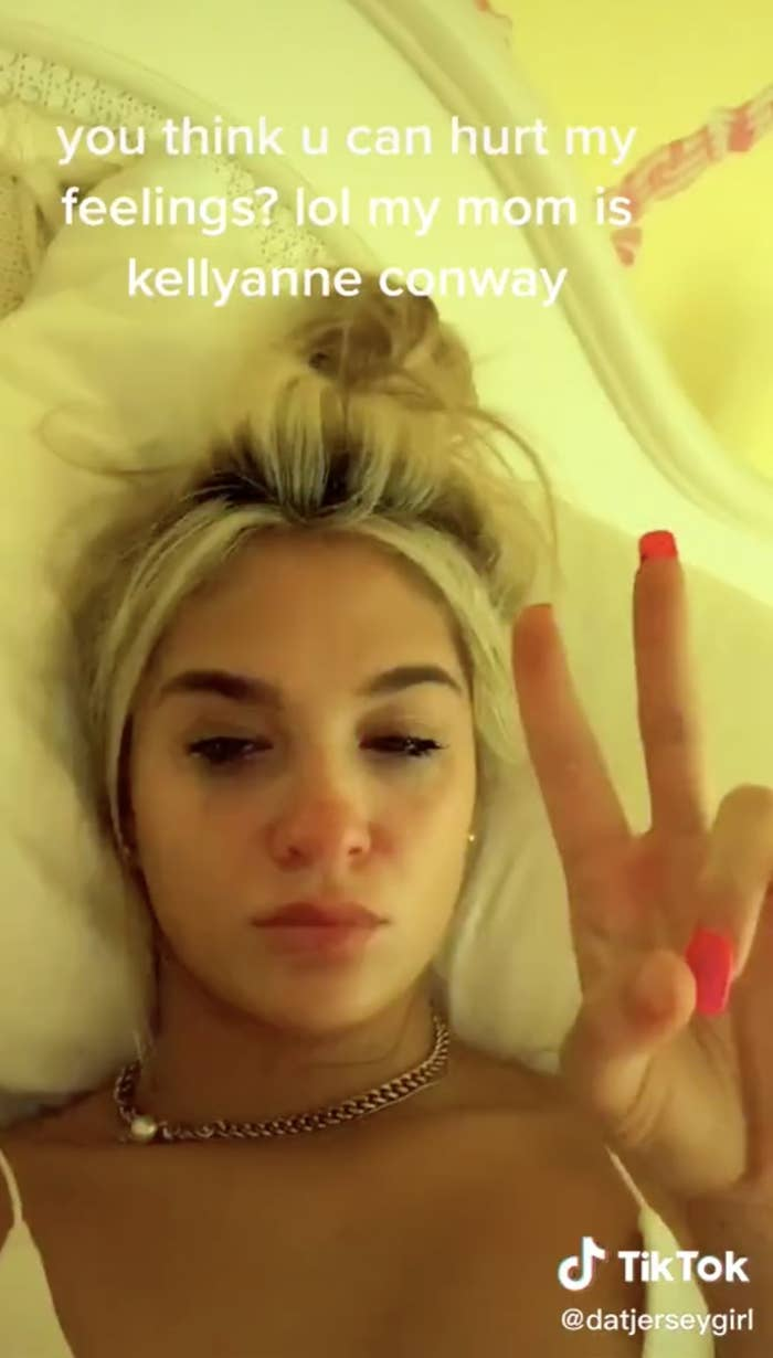 "Screenshot from Claudia's TikTok making the ""peace"" sign gesture"