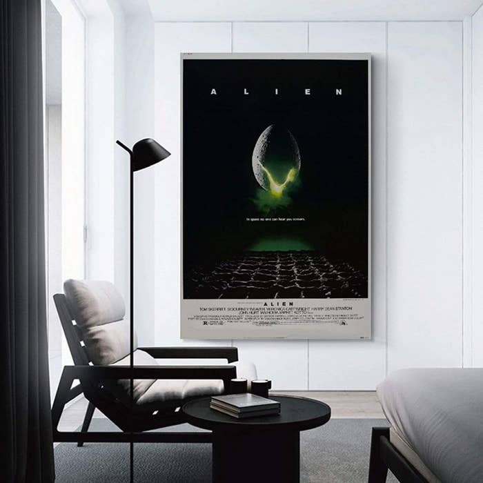 The Alien movie poster hung up on a wall in a living room