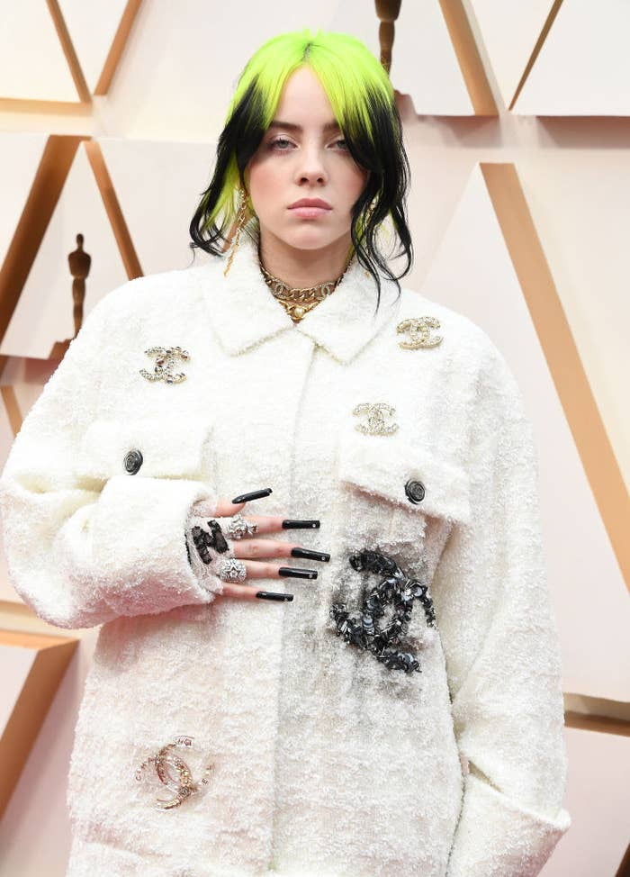 Billie Eilish posing on a red carpet wearing matching Chanel jacket and pants featuring several brooches shaped into the iconic interlocking double C