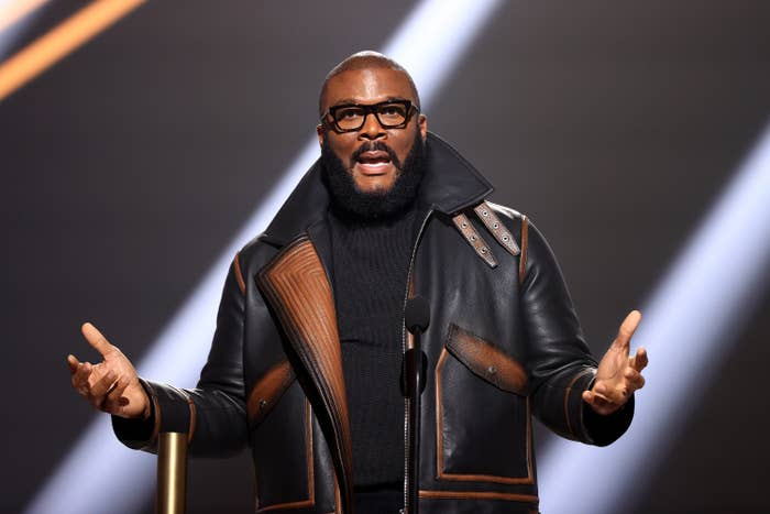 Tyler Perry accepts People's Champion Award onstage for the 2020 E! People's Choice Awards wearing a leather jacket and a turtleneck