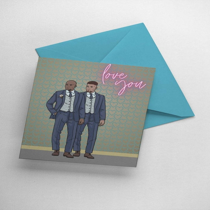 """Card with two people in suits with the words """"love you"""" in neon in the corner"""
