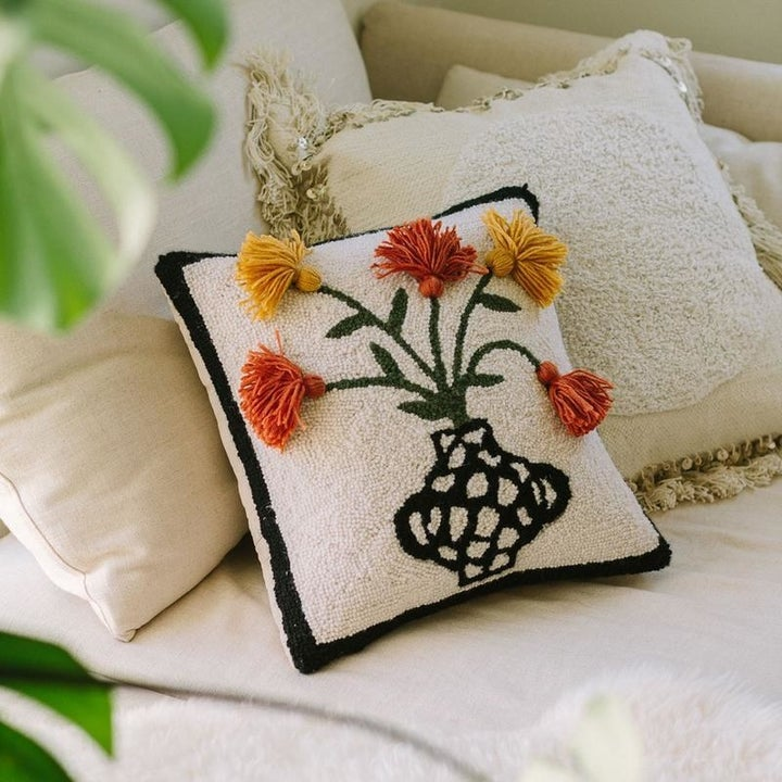 Square throw pillow with decorative vase pattern and three dimensional flowers