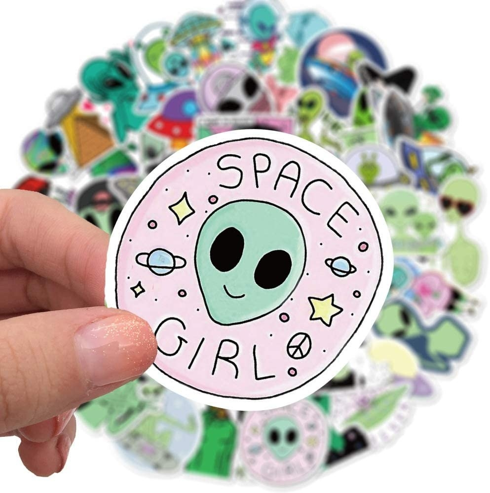 A person holding a cute alien sticker that says space girl on it