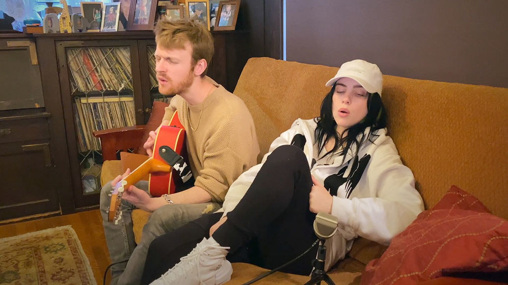 Billie and Finneas, who's playing a guitar, sitting on a couch recording a song