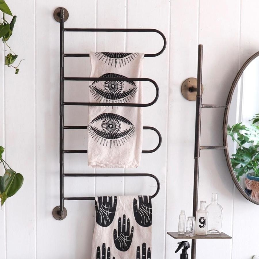 the rotating hanging rack towel bar mounted on a bathroom wall with linen towels hanging from several of its bars