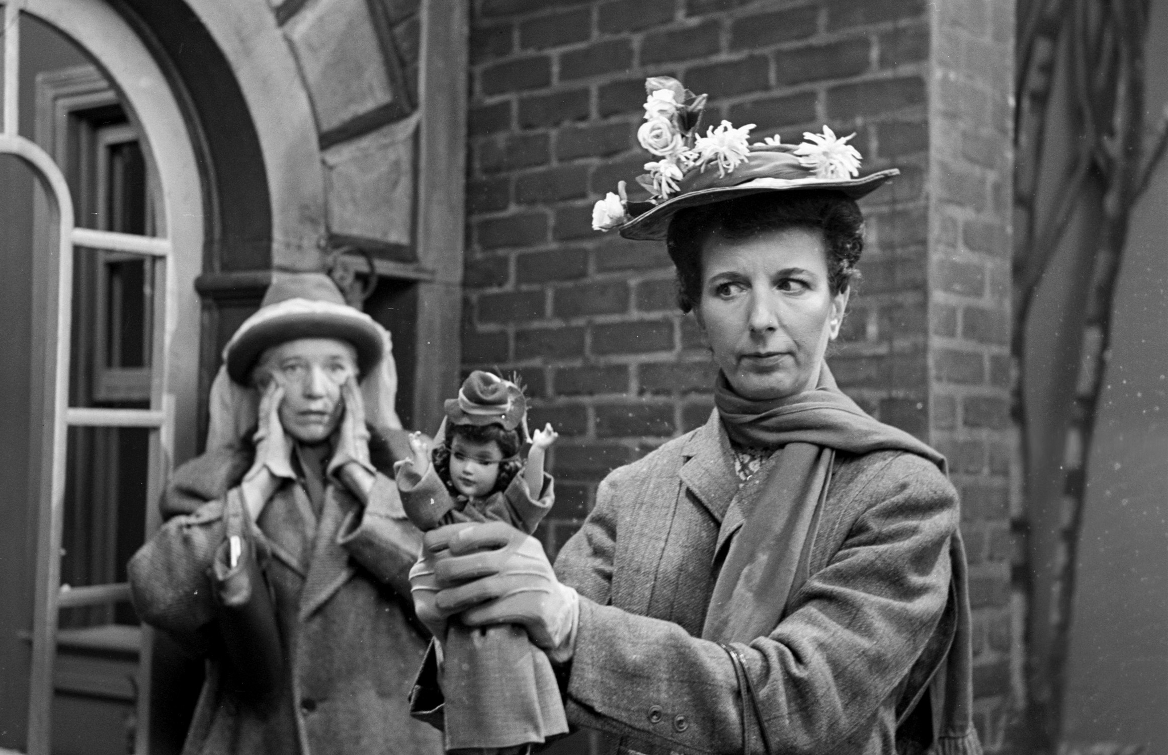 A photo of Mary Wickes holding a doll dressed as Mary Poppins