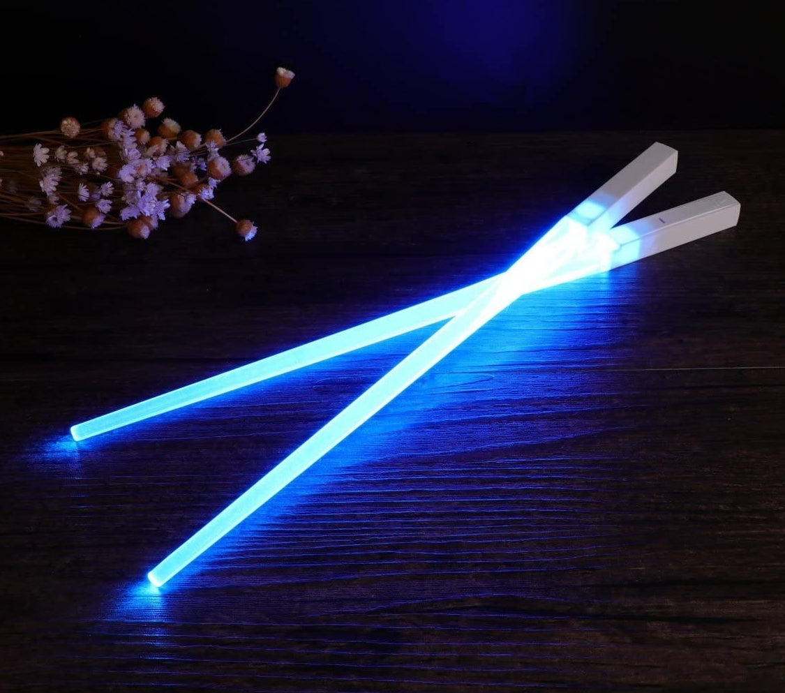 Glowing lightsaber chopsticks on a table