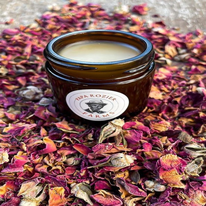 Rose balm inside apothecary jar with rose petals all around it