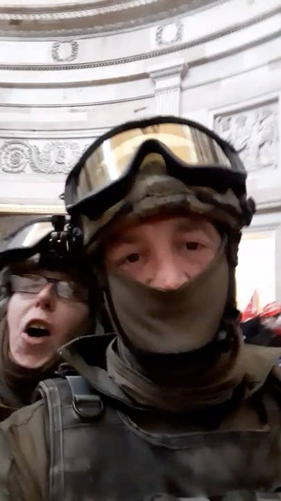 Two people, wearing military-style gear, including face coverings and goggles, take a blurry selfie