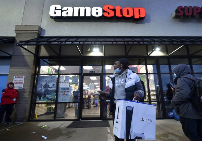A man wearing a face mask leaves a Game Stop store with a PlayStation 5 box