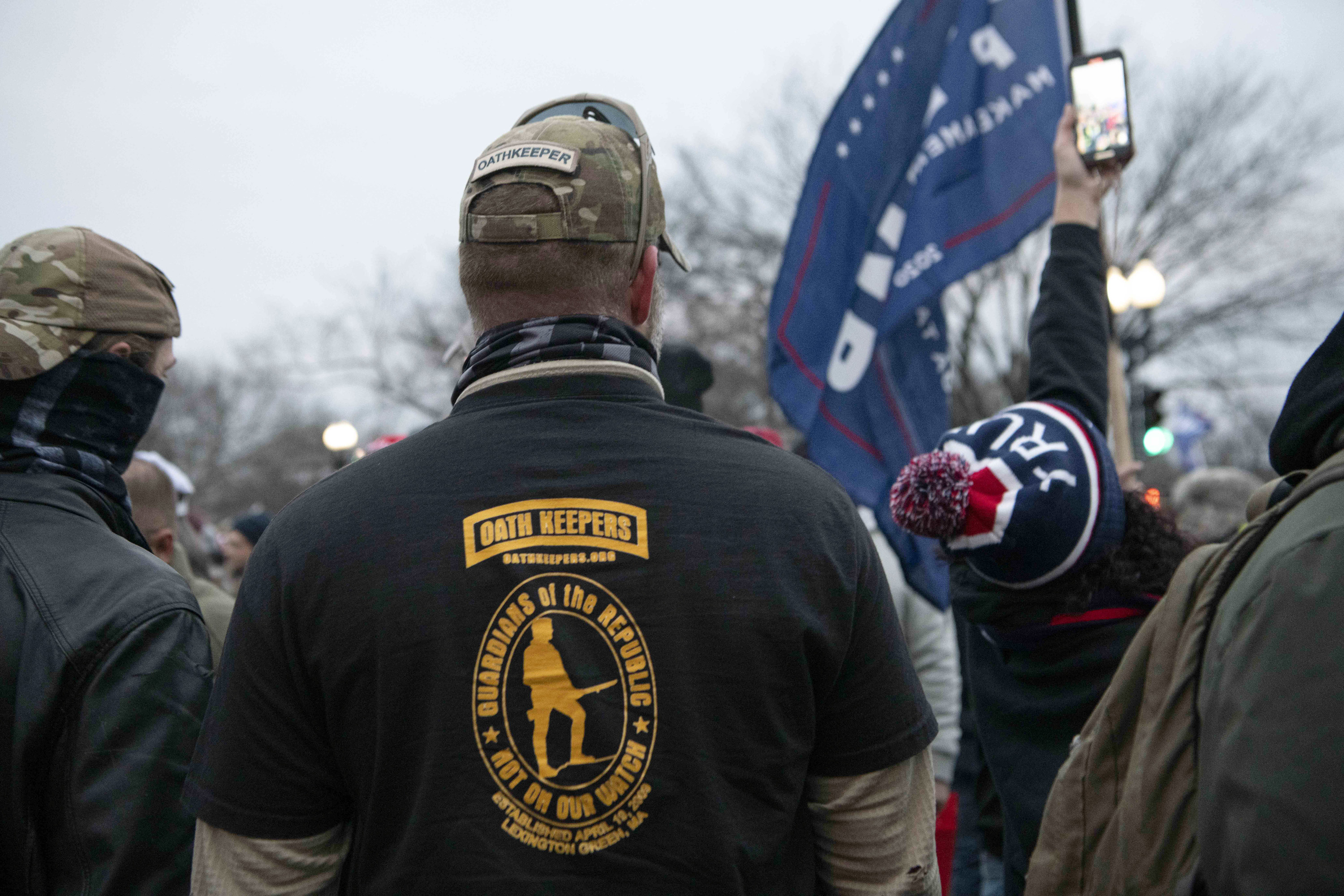 "A man with his back to the camera wears a T-shirt that reads ""Oath Keepers: Guardians of the Republic — Not on Our Watch"""