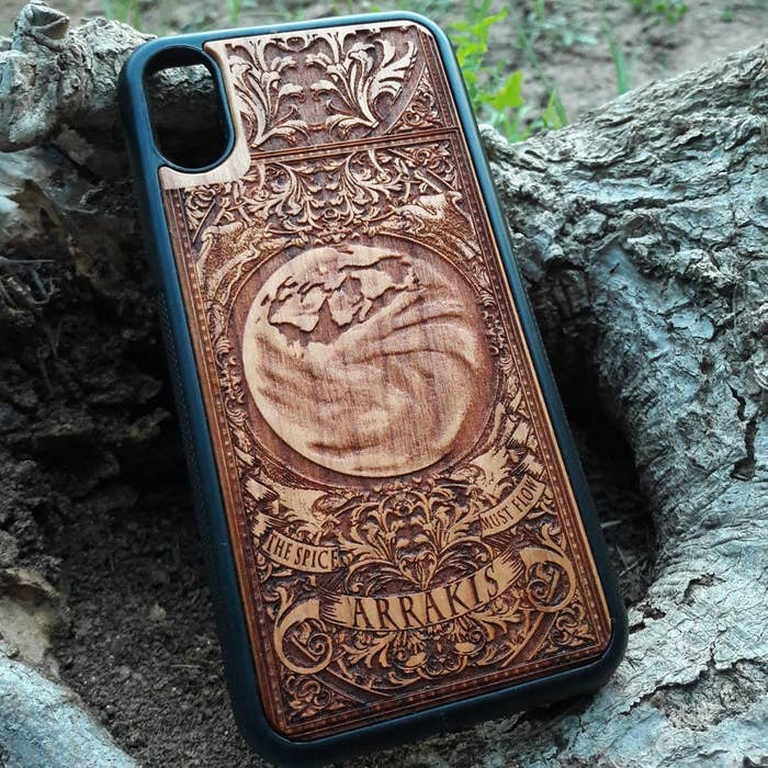 An intricately carved wooden phone case based on Dune
