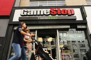 A couple pushing a stroller walk past a GameStop store