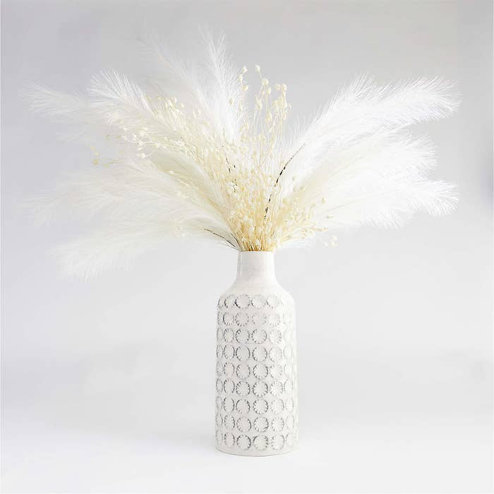 White vase with pampas grass inside