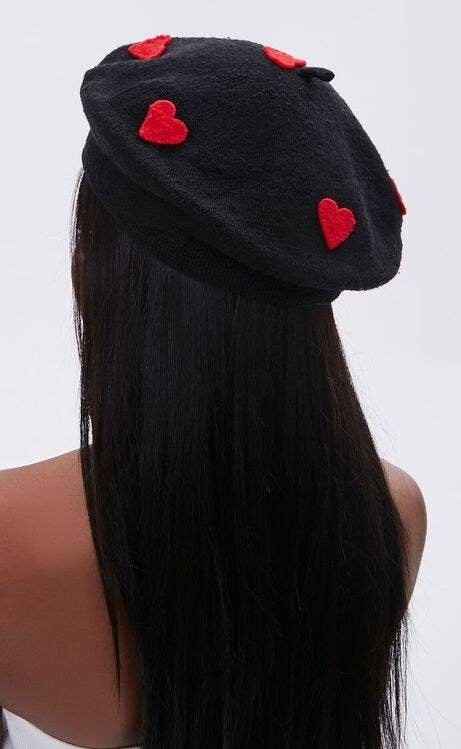 Model wearing black beret with red hearts