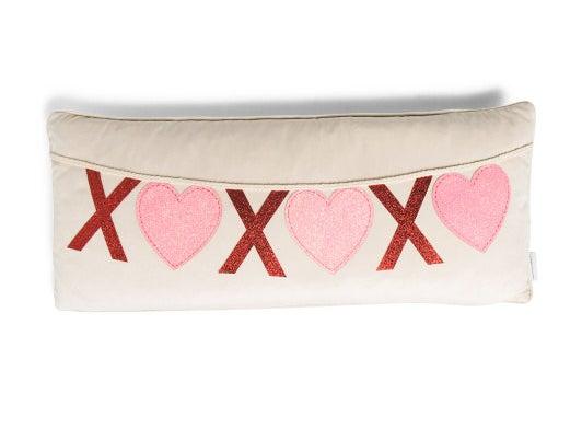 "a tan lumbar pillow with an ""xoxo"" designed banner across it"