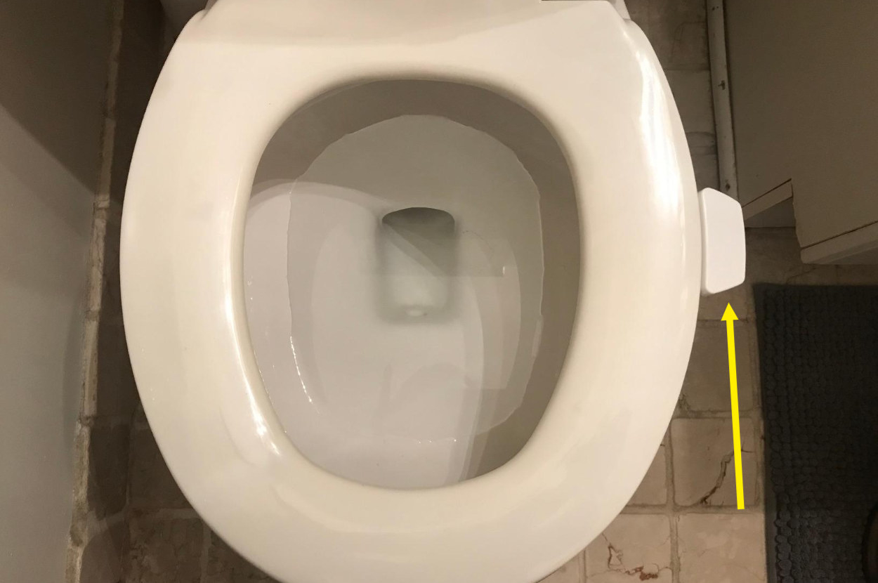 White toilet seat lifter attached to toilet seat