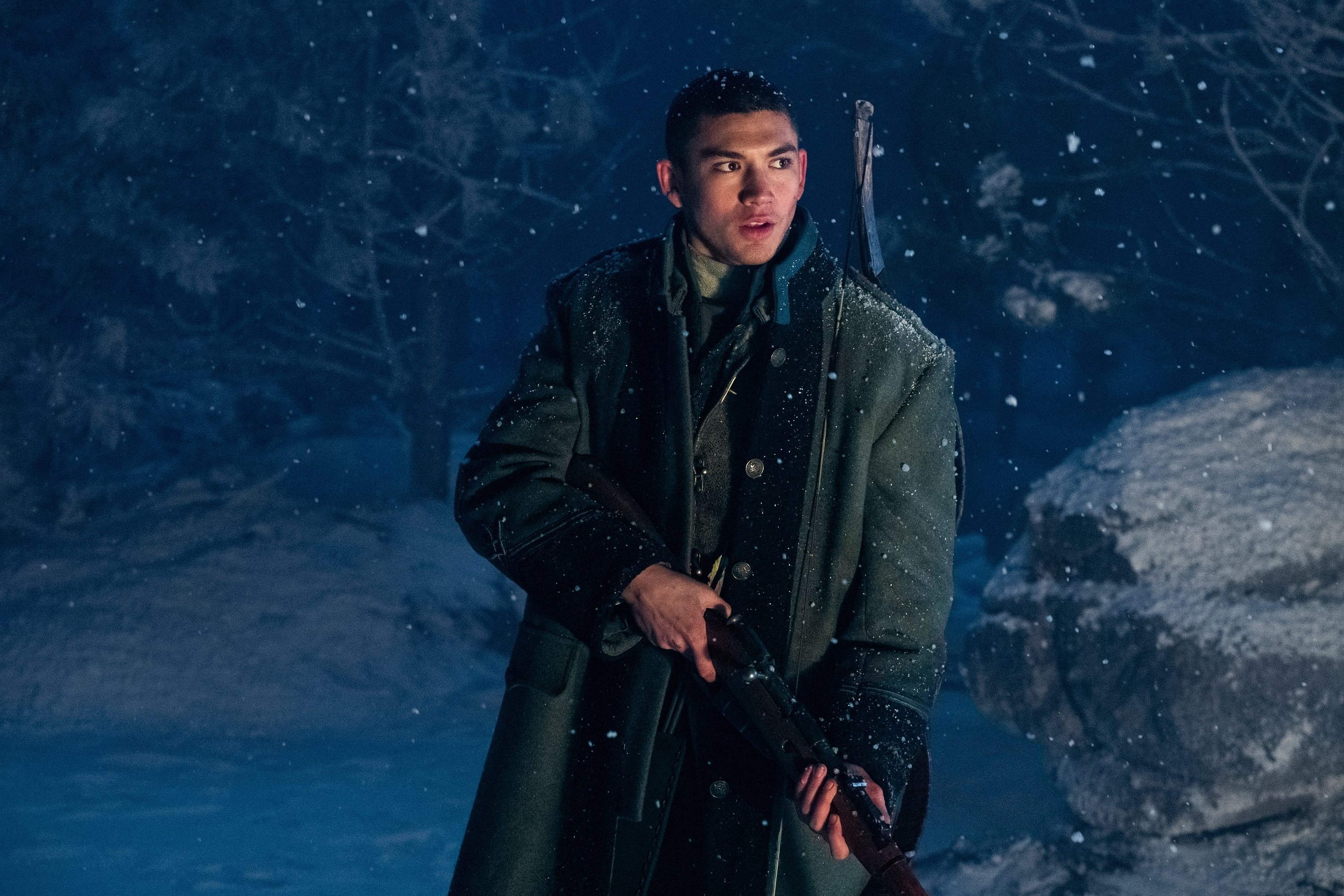 Archie Renaux as Malyen Oretsev holding a gun in a snow-y clearing