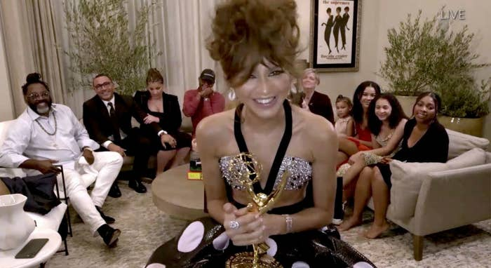 Zendaya, at home, holding her Emmy while wearing a two piece rhinestone and polka dot gown.