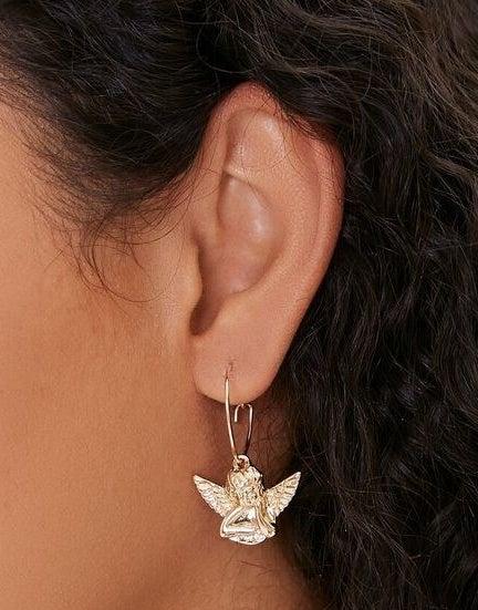 Model wearing gold angel earrings