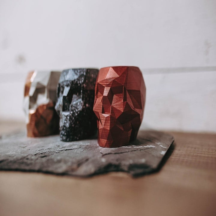 Skull shaped pencil holders in red, speckled black, and foil