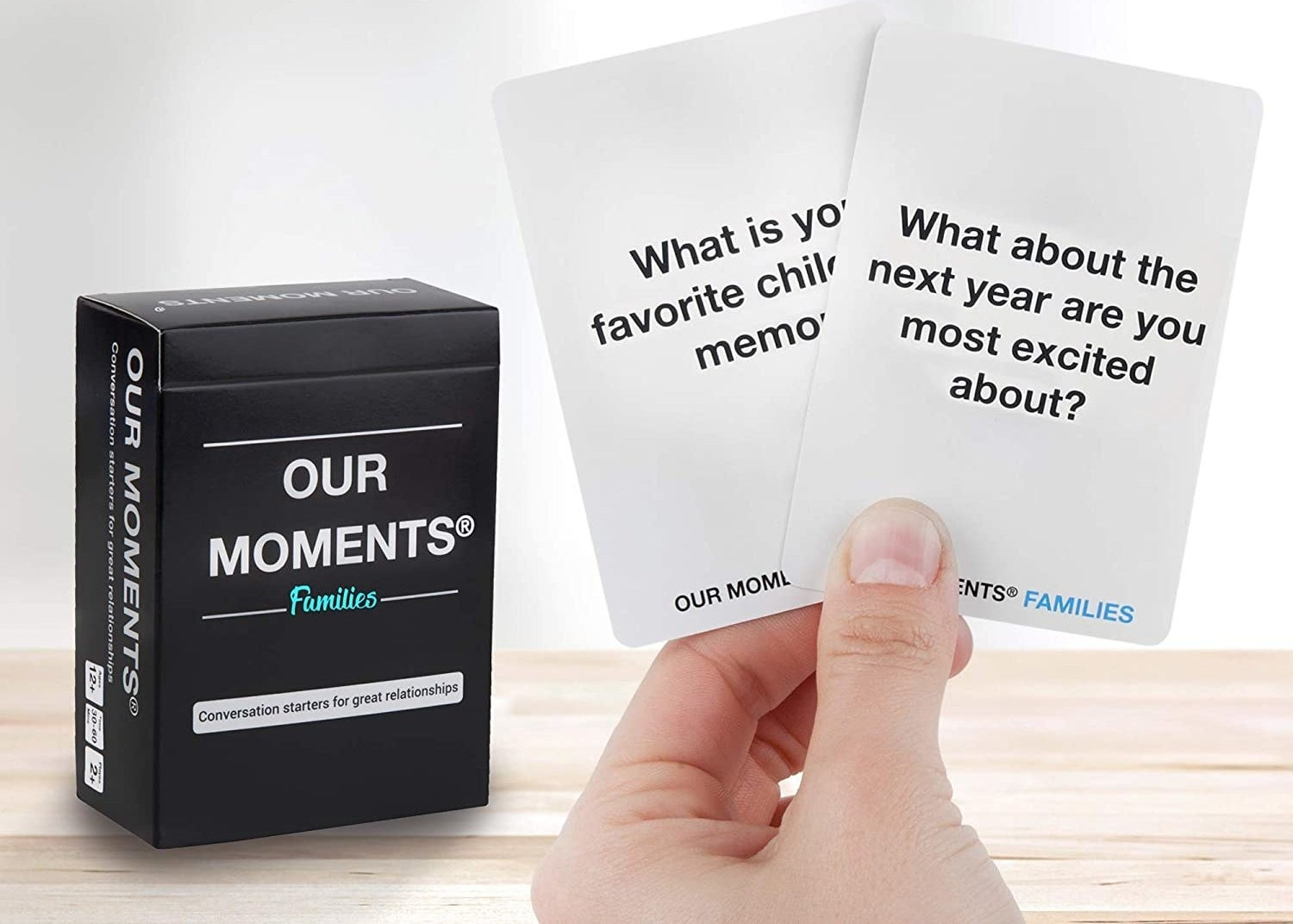 person holding two cards from the box that say what is your favourite childhood memory and what about the next year are you most excited about