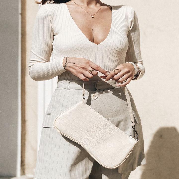 model holding baguette bag in ivory