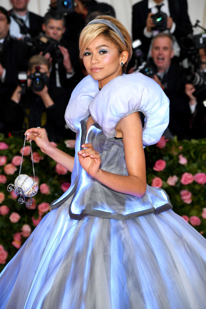 Zendaya arriving at the Met Gala in a glowing light up princess gown with a wig and pumpkin shaped purse.