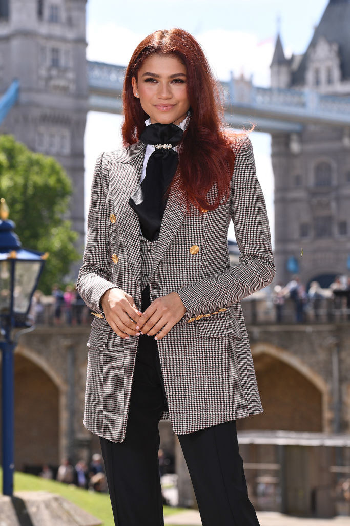 Zendaya standing outside in London with a tweed blazer, vest, ascott tied around her neck, and dress pants.