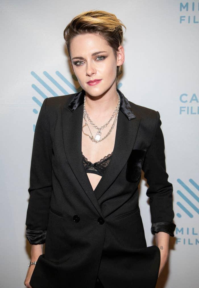 Kristen posing for a photo wearing a long blazer with her bra peeking through and matching pants