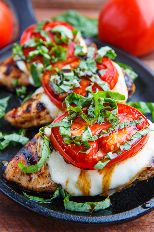 Three pieces of grilled chicken topped with mozzarella, tomato, basil, and balsamic drizzle.