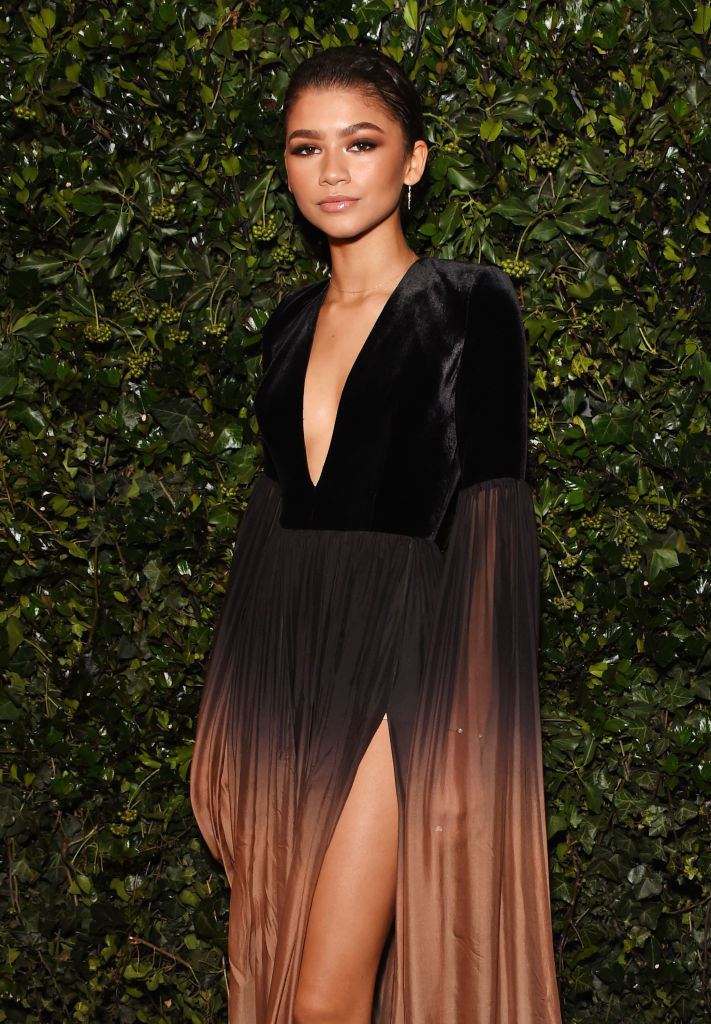 Zendaya posing in a flowy dress that changes color at the bottom.